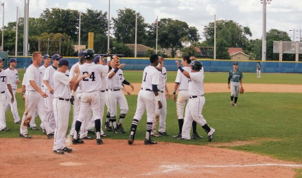 Julio Bautista is greeted by his teammates after his drove in the tenth run to secure Taravella's victory.